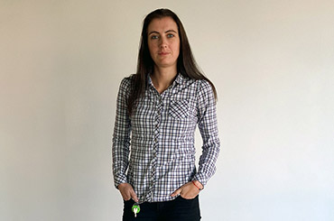 Telerik Academy graduate in shirt with square pattern in front of a white wall at Tick42's office