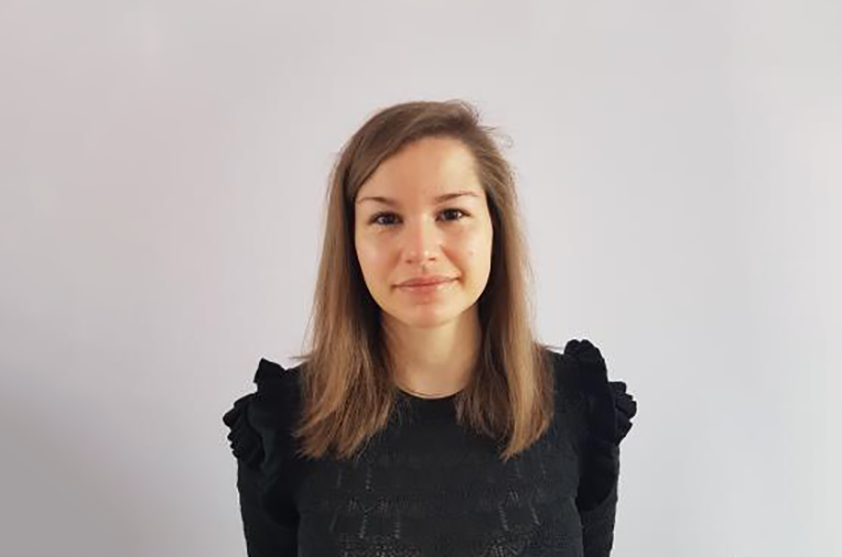photo of liliya in front of a grey wall with telerik academy visual element added