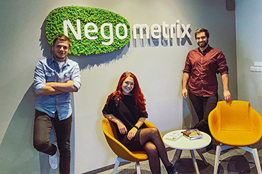 Three people in a office environment with sign Negometrix on green background