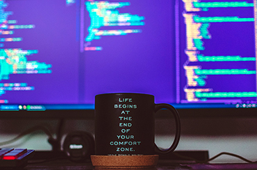 photo of a mug in front of a monitor with code