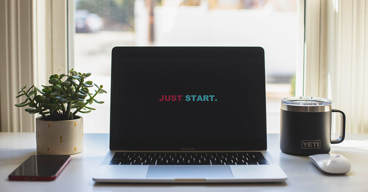 "Laptop on a table with a sign ""Just start"""