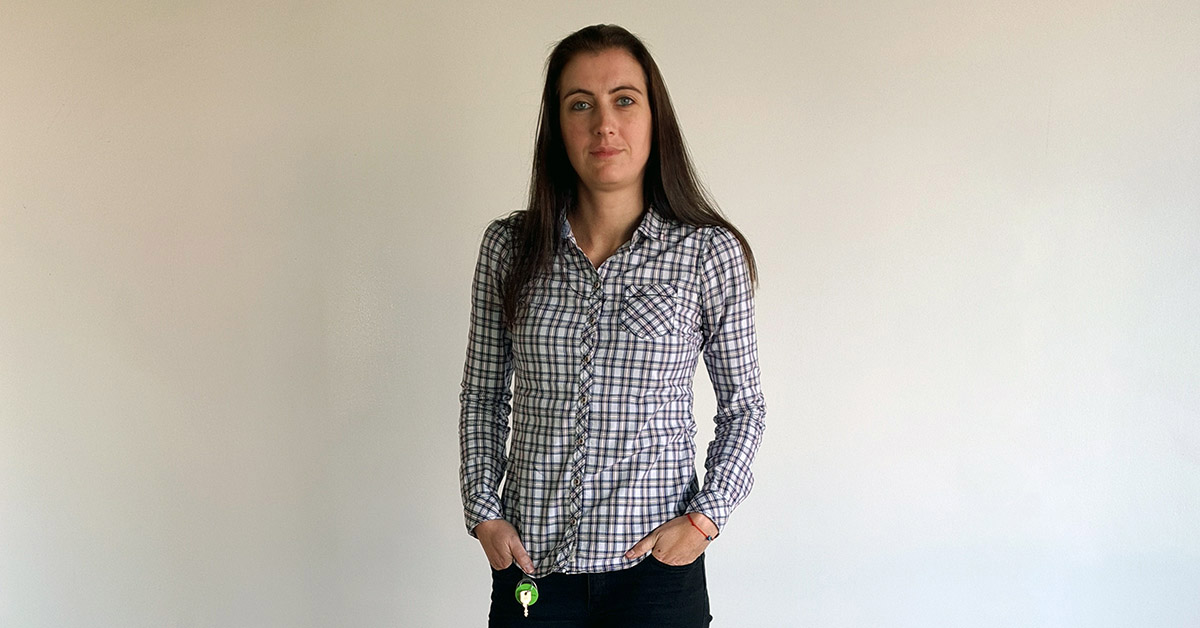 Telerik Academy Alpha graduate in a shirt with square pattern in front of a white wall at Tick42's office