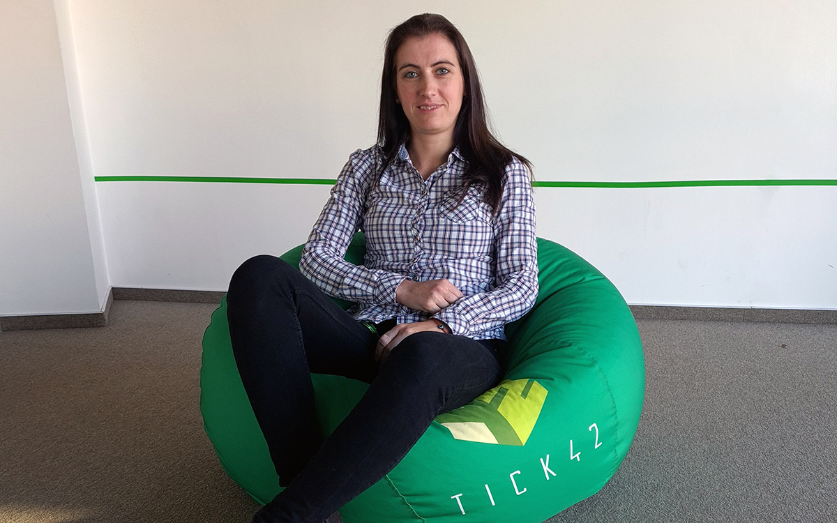 Telerik Academy Alpha graduate in a shirt with square pattern sitting on a green pouf with Tick42 logo on it