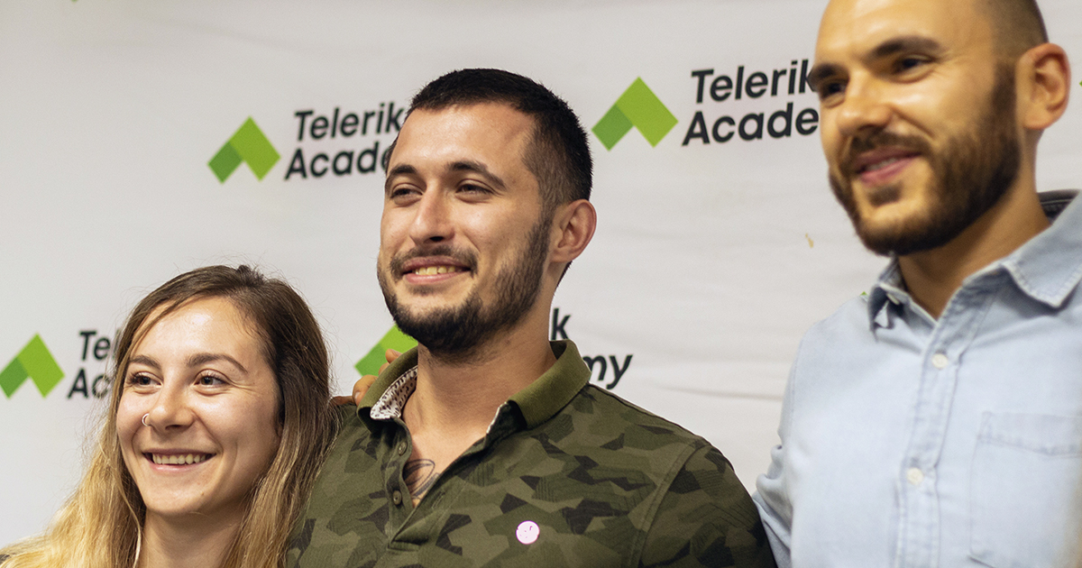 Photo of Daniel and two of his trainers during his graduation in front of a wall with telerik academy's logo on it